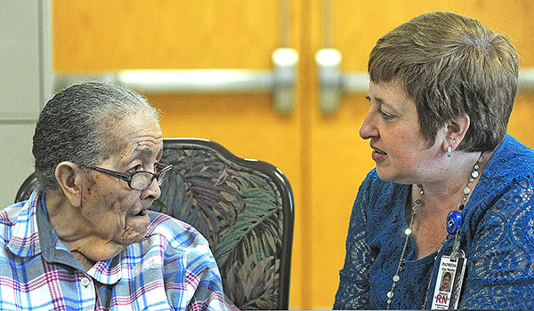 Patricia Cultrara, director of the Adult Day Health Care Program at Sisters of Charity Hospital, speaks to 87-year-old Essie Cooper about the program. (Dan Cappellazzo/Staff Photographer)