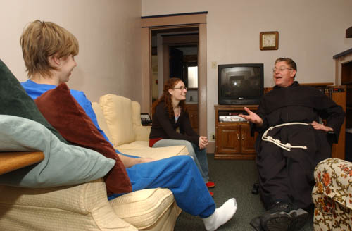 In 2006, `Dave` a resident at the Franciscan Center talks with Nicole Carroll, emergency shelter house coordinator, and Father Joseph Bayne, OFM, Conv. The Franciscan Center is a dual runaway homeless youth shelter that was started in 1980.