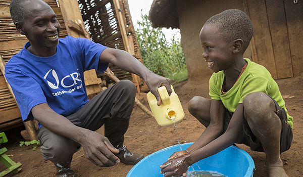 Kiplangat Hosea (right), 8, washes his hands during a hygiene sensitization session by Catholic Relief Services community mobilizer Akusuro John in Bukwo District, Uganda. CRS recently helped implement WASH (water, sanitation and hygiene) interventions in the village. (Jake Lyell/Catholic Relief Services)