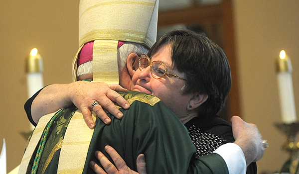 An emotional Deborah Brown hugs Bishop Richard J. Malone during a Mass where Brown was appointed as Pastoral Administrator of Saint John the Baptist Parish, Alden. Brown is the first non-religious woman to run a parish in the diocese. (Dan Cappellazzo/Staff Photographer)