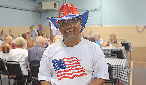 Father George Devanapalle, administrator at SS. Joachim & Anne Church, Attica, is all smiles during luncheon at St. Vincent Auditorium celebrating his U.S. citizenship. (Dan Cappellazzo/Staff Photographer)