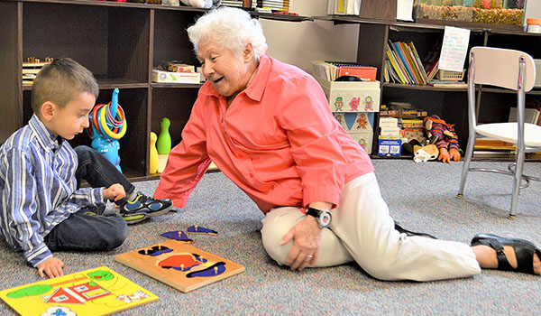 Sister Maralynn Sciarrino, RSM, enjoys a game with 4-and-a-half-year-old Giani Rizzo to help improve his speech at Mercy Speech Center in Buffalo. The Mercy Speech Center closed this summer after two local sisters retired. (Courtesy of Gary Loncki)
