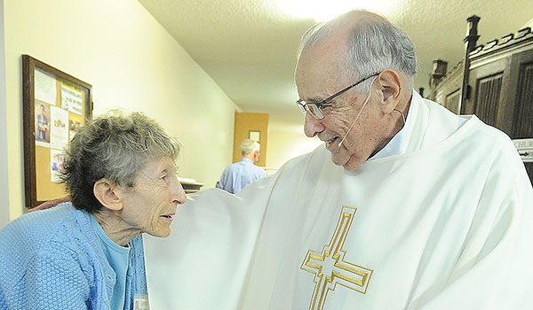 Retired priest Msgr. Angelo Caligiuri, 84, speaks with volunteer Cynthia DiMartina after Mass at St. Joseph University Church. A special collection will be held for the retired priests fund on Aug. 6. (Dan Cappellazzo/Staff Photographer)