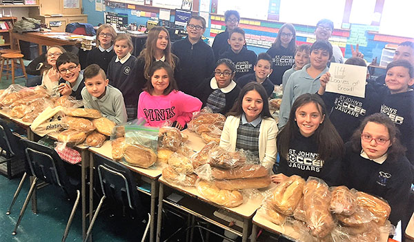 St. John's fifth-grade with some of the 114 loaves of bread they baked. (Courtesy of St. John the Baptist School)