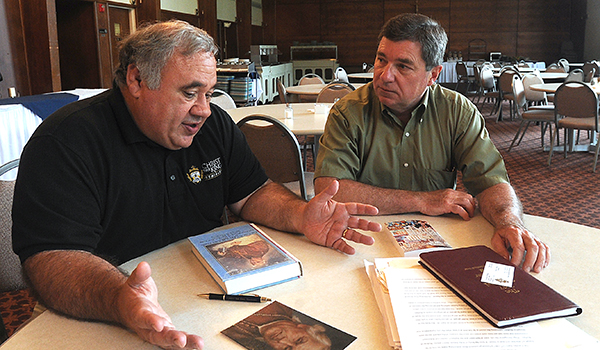 Christ the King Seminary professors Dennis Castillo and Paul Lubienecki look over material about Bishop John Timon in preparation for a program they are hosting at the seminary dining hall this September. (Dan Cappellazzo/Staff Photographer)