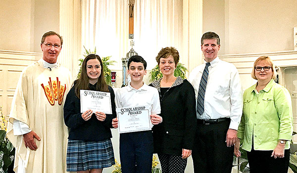 The Briana Talty Memorial Scholarship is awarded to Alyssa Barnum (second from left) and Colin Richey (third from left) at St. John the Baptist School in Kenmore. Joining them are Father Michael Parker (left), Dawne and Tom Talty (third and second from right) and Principal Cynthia Jacobs (right). (Courtesy of St. John the Baptist School)