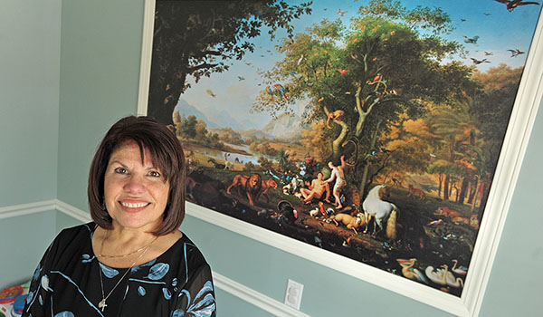 Gloria M. Roetzer, MD, owner of Trinity Pediatrics, stands in her waiting room in front of a print of Adam and Eve. Roetzer opened her practice to combine Catholic teaching and medical care. (Dan Cappellazzo/Staff Photographer)
