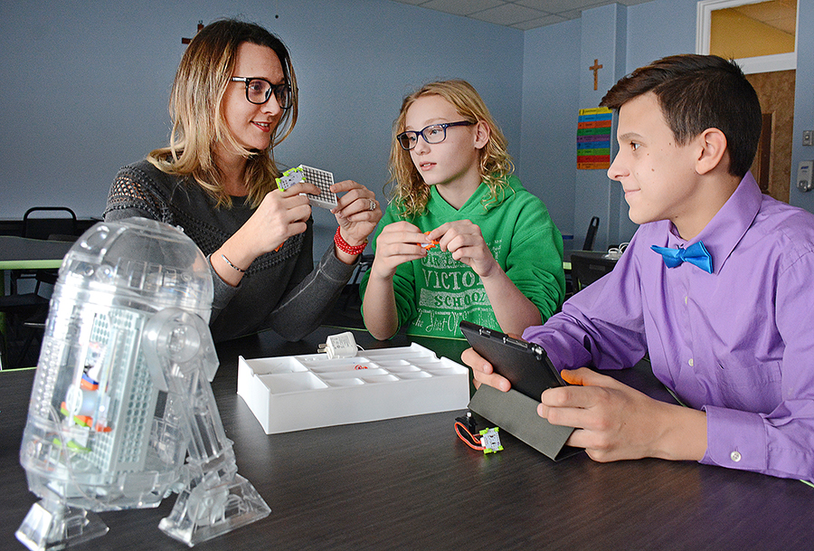 Alongside a model of R2D2 created by OLV School students,Tech Integration Specialist Rebecca Roussev with sixth-grader Sophie Judasz and eighth-grader Matt Viverto in the school's new tech lab. (Dan Cappellazzo/Staff photographer)