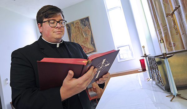Deacon Paul Cygan looks the Bible over in the Christ the King Seminary administration building chapel. Deacon Cygan along with three others will be ordained at St. Joseph Cathedral in June. (Dan Cappellazzo/Staff Photographer)