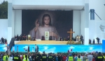 Pope Francis and Polish dignitaries sit in front of an copy of the Divine Mercy icon. The pope made his first public appearance of World Youth Day at a welcoming ceremony, to deliver a message of encouragement to teen and young adult Catholics from around